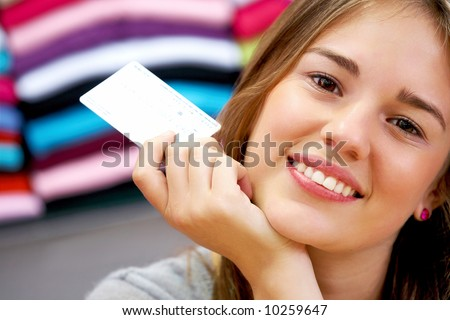 woman smiling and holding a credit card in a shop - stock photo