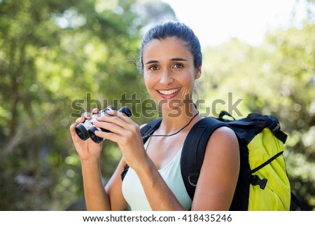 Woman smiling and holding binoculars on the wood - stock photo