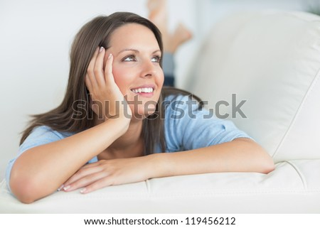 Woman smiling and looking away in the living room - stock photo