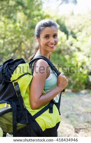 Woman smiling and posing with her backpack on the wood - stock photo