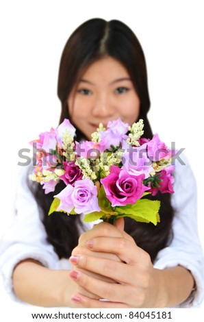 Woman smiling and showing flowers isolated on white background - stock photo