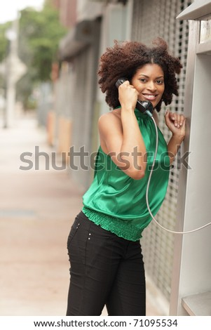Woman smiling and talking on a pay phone