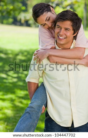 Woman smiling as she watches her friend while he carries her around on his back - stock photo