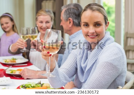 Woman smiling at camera while holding a glass of wine at home in the living room - stock photo