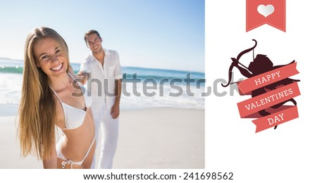 Woman smiling at camera with boyfriend holding her hand against happy valentines day - stock photo