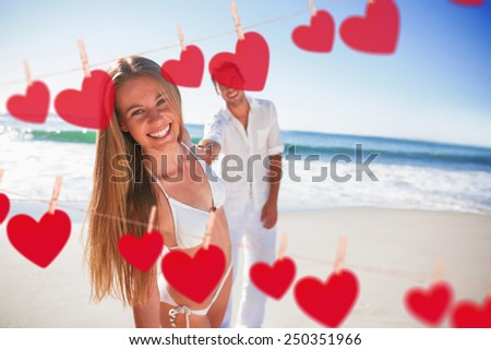 Woman smiling at camera with boyfriend holding her hand against hearts hanging on a line - stock photo