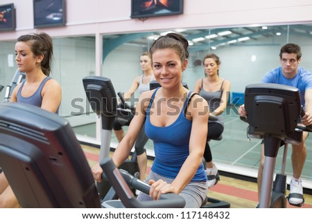 Woman smiling at spinning class in gym - stock photo