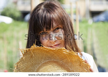 woman smiling hidden behind a straw hat - stock photo
