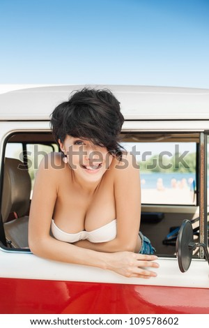 Woman smiling in car near the beach - outdoors - stock photo