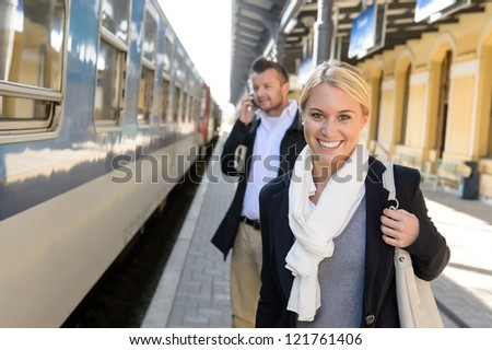Woman smiling in train station man talking on cellphone commuters - stock photo