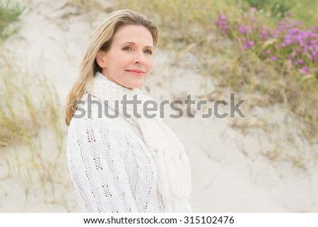 Woman smiling near the sandy hill at the beach - stock photo