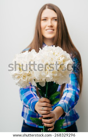Woman smiling showing flowers isolated on white background. Beautiful fresh young mixed race Asian Caucasian female model in cute summer dress. - stock photo