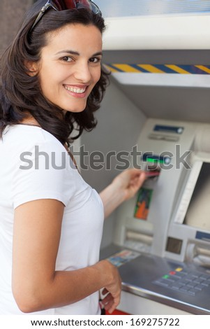 woman smiling while withdrawing cash at ATM  - stock photo