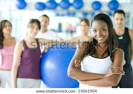 woman smiling with a group of gym people on the background - stock photo