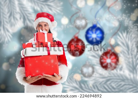 Woman smiling with christmas presents against baubles hanging over christmas scene - stock photo