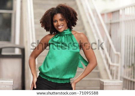 Woman smiling with hands on hips - stock photo