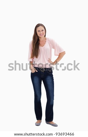 Woman smiling with her hand on the hip and the other hand in her pocket against white background