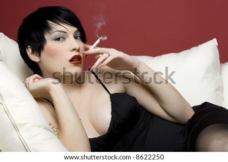 Woman smoking a cigarette on white sofa. - stock photo