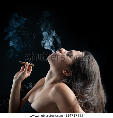 Woman smoking cigar against dark background. Studio fashion photo. - stock photo
