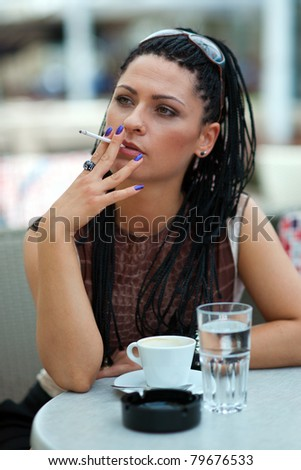 woman smoking cigarette outiside in coffee bar - stock photo