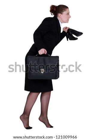 Woman sneaking out of the office - stock photo