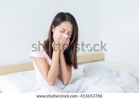 Woman sneezing in her bed