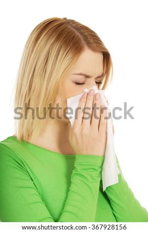 Woman sneezing to tissue. - stock photo
