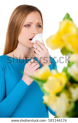 Woman sneezing. Young woman holding handkerchief near face and sneezing while standing isolated on white - stock photo