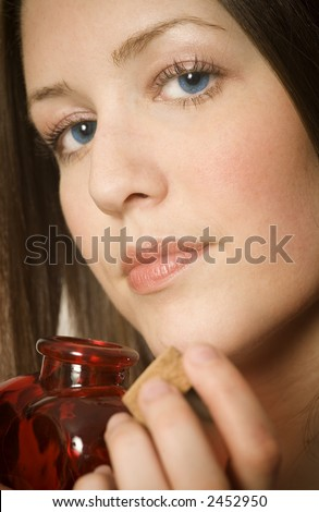 Woman sniffing perfume in heart shaped bottle