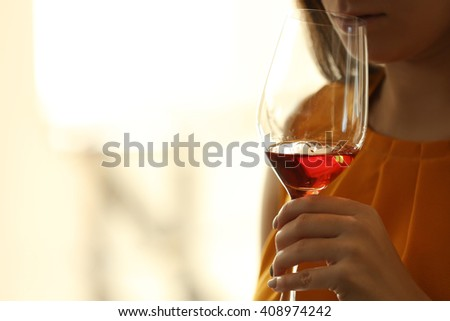 Woman sniffing red wine in a glass, close up - stock photo
