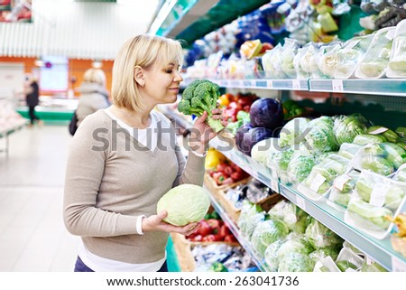 Woman sniffs broccoli and holds white cabbage in the store - stock photo