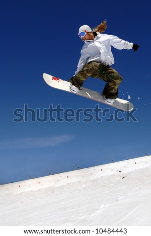 Woman snowboarder in mid-air with blue sky