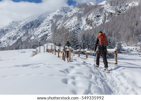 Woman snowshoeing on path at Valnontey, near Cogne in Aosta Valley