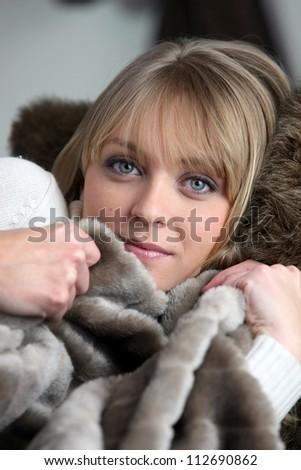 Woman snug on a sofa - stock photo
