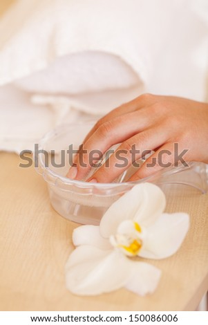 Woman soaking her nails before a manicure in a beauty salon or spa - stock photo