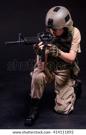 Woman soldier in helmet aiming from rifle black background/Female soldier aiming from rifle