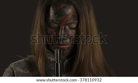 Woman soldier war camouflage closed eyes in dark background - stock photo