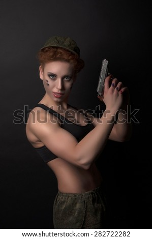woman soldier with a gun on a black background - stock photo