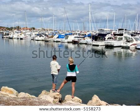 woman & son fishing at waterfront - stock photo