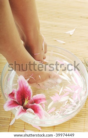 woman spa pedicure foot treatment with water and flower