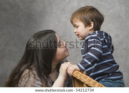 Woman speaking with her little child, studio shot - stock photo