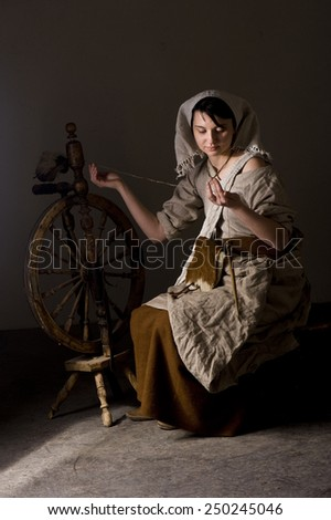 Woman spinning on the great or walking wheel - stock photo