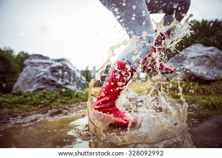 Woman splashing in muddy puddles in the countryside - stock photo