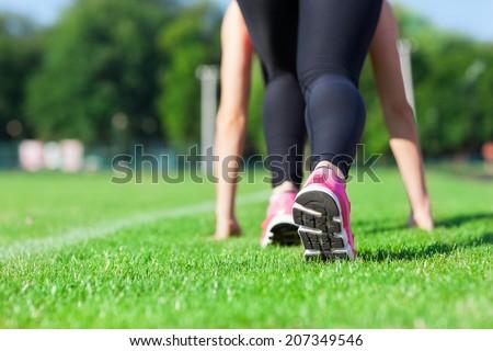 Woman sport run on stadium green grass concept, fitness girl runner feet in start position closeup on shoe, morning outdoor jog training workout - stock photo