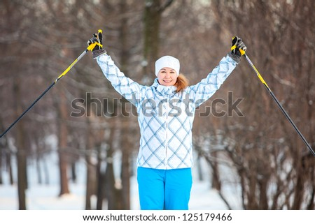 Woman sportsman on cross ski with hands up - stock photo