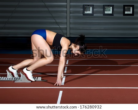 Woman sprinter leaps from starting block. - stock photo