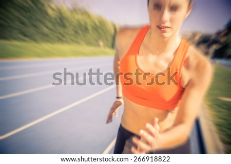 Woman sprinting on a running track - Female athlete running with a motion blur effect - stock photo