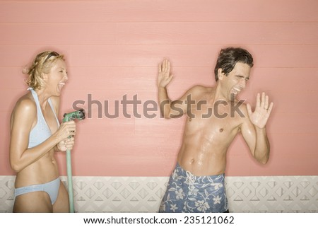 Woman Squirting Man with Water - stock photo