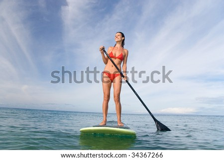 woman stand up paddle board smiling - stock photo