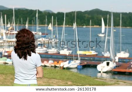 woman standing alone on marina, longing girl in solitude, secret fatal girl - stock photo